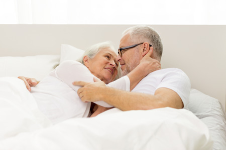 man woman kissing: family, bedtime, resting, age and people concept - happy senior coupler lying in bad at home Stock Photo