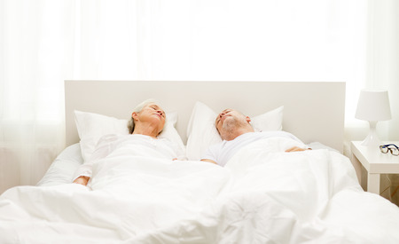 senior living: family, bedtime, resting, age and people concept - happy senior coupler lying in bad at home Stock Photo