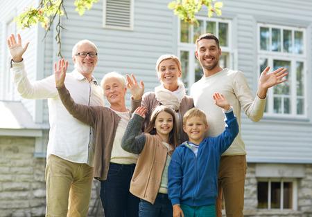 gebaar, geluk, generatie, huis en mensen concept - gelukkige familie wuivende handen in de voorkant van het huis buiten