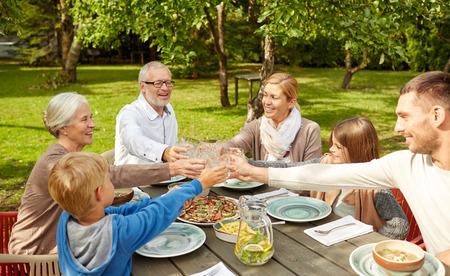 personas celebrando: familia, generaci�n, hogar, vacaciones y concepto de la gente - familia feliz cena y tintineo de vasos en el jard�n de verano