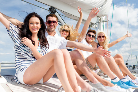 cruise: vacation, travel, sea, friendship and people concept - smiling friends sitting on yacht deck and greeting