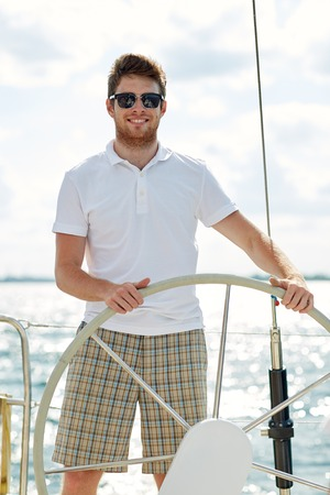 tripping: vacation, holidays, travel, sea and people concept - young man in sunglasses steering wheel on yacht