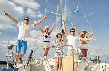 boat party: vacation, travel, sea, friendship and people concept - smiling friends sitting on yacht deck and greeting