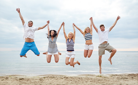 happy people jumping: summer, holidays, sea, tourism and people concept - group of smiling friends in sunglasses walking on beach Stock Photo