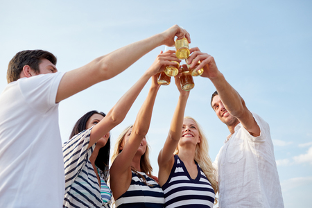nonalcoholic beer: summer, holidays, tourism, drinks and people concept - group of smiling friends clinking bottles of beer or cider on beach