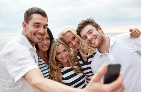 summer, sea, tourism, technology and people concept - group of smiling friends with smartphone on beach photographing and taking selfie photo