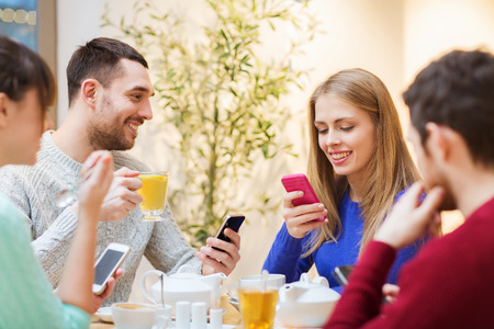 cell phone addiction: people, leisure, friendship and technology concept - group of happy friends with smartphones meeting at cafe and drinking tea Stock Photo