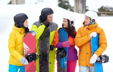 winter, leisure, extreme sport, friendship and people concept - happy friends in helmets with snowboards talking photo