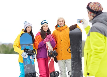 winter sport, technology, leisure, friendship and people concept - happy friends with snowboards and smartphone taking picture outdoors photo