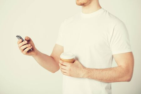 free time: man with smartphone and take away coffee cup
