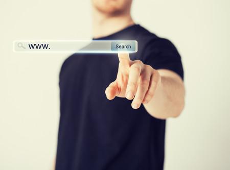 technologie, zoeken systeem en internet concept - mannelijke hand te drukken knop Zoeken Stockfoto