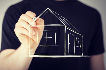 Bienes raíces, tecnología y alojamiento - imagen del hombre que drena una casa en la pantalla virtual Foto de archivo - 37671145