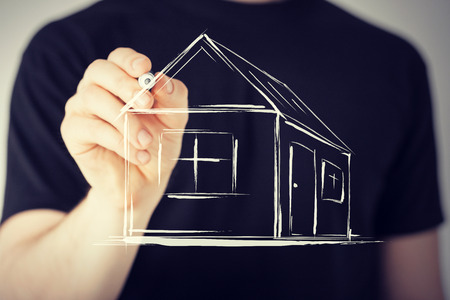 real estate agent: real estate, technology and accomodation - picture of man drawing a house on virtual screen