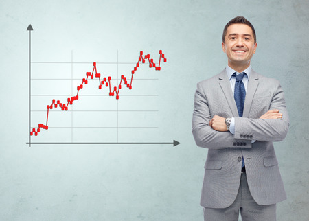business, people, economics, stock market and finances concept - happy smiling businessman in suit with forex chart over gray background