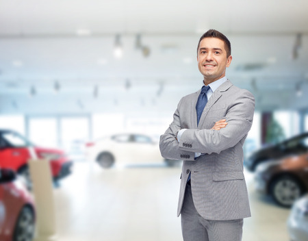salon background: business, car sale, consumerism and people concept - happy man over auto show or salon background Stock Photo