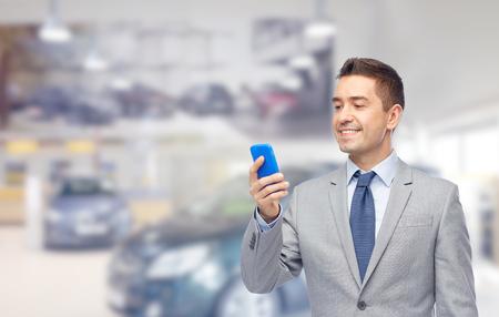 ビジネス、車販売、人と技術のコンセプト-自動ショーやサロンの背景にスマート フォンに満足している実業家テキスト メッセージ