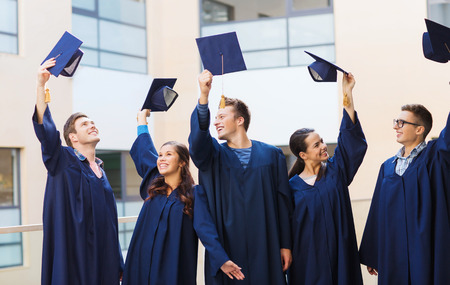 graduation hats: education, graduation and people concept - group of smiling students in gowns waving mortarboards outdoors