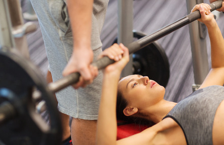 sport, fitness, teamwork, weightlifting and people concept - young woman and personal trainer with barbell flexing muscles in gym photo