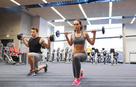 athletic: sport, bodybuilding, lifestyle and people concept - young man and woman with barbell flexing muscles and making shoulder press lunge in gym