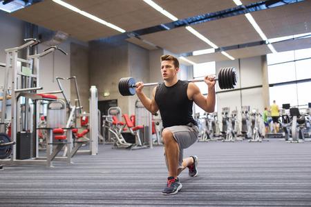 deporte, culturismo, estilo de vida y concepto de la gente - hombre joven con la barra a flexionar los músculos y hacer press de hombros estocada en el gimnasio