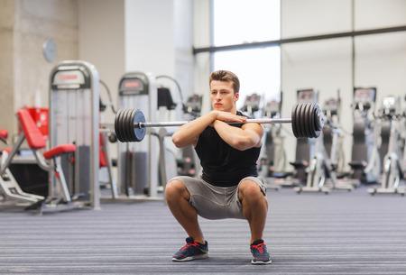 hombre fuerte: deporte, culturismo, estilo de vida y concepto de la gente - hombre joven con mancuerna haciendo sentadillas en el gimnasio