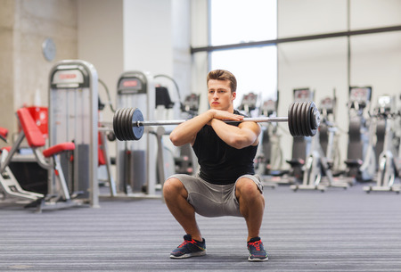 man lifting weights: sport, bodybuilding, lifestyle and people concept - young man with barbell doing squats in gym