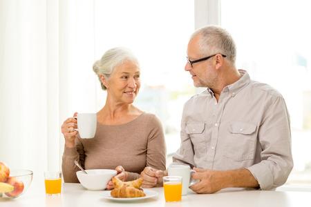 alimentos y bebidas: familia, tecnolog�a, alimentos, bebidas y concepto de la gente - feliz pareja mayor de desayunar en casa