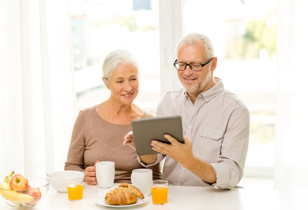 senior eating: family, technology, food, drinks and people concept - happy senior couple with tablet pc computer having breakfast at home