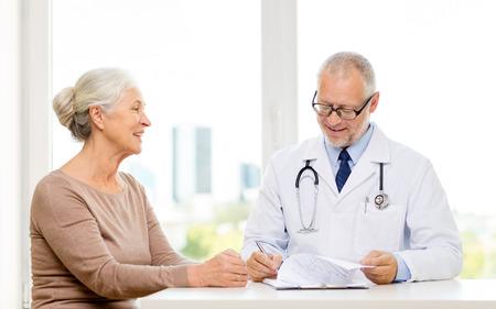 seniors: la medicina, la edad, la salud y las personas concepto - sonriendo reuni�n mujer mayor y el m�dico en el consultorio m�dico