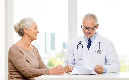 old woman: medicine, age, health care and people concept - smiling senior woman and doctor meeting in medical office