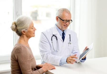 geneeskunde, de leeftijd, de gezondheidszorg en de mensen concept - lachende senior vrouw en arts met tablet pc computer bijeenkomst in medische kantoor