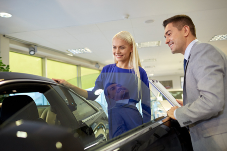 open car door: auto business, car sale, consumerism and people concept - happy woman with car dealer in auto show or salon Stock Photo