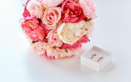 female bonding: wedding rings in little box and flower bunch on table