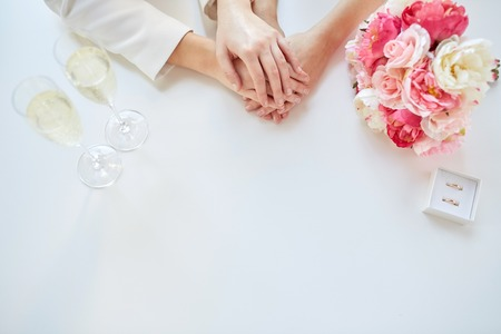 close up of happy couple hands with flower bunch, champagne glasses and wedding rings