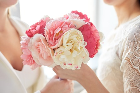 feminine hands: close up of happy married lesbian couple with flower bunch Stock Photo