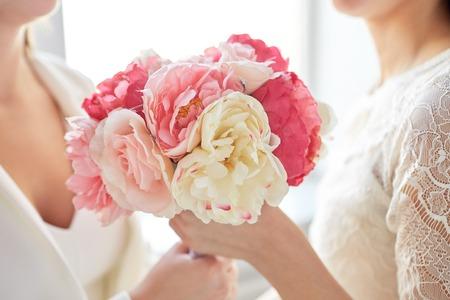 lesbienne: fermer des heureux couple marié de lesbiennes avec bouquet de fleurs