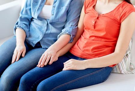 personnes, l'homosexualité, le mariage de même sexe, le concept d'amour gay et - à proximité d'heureux couple de lesbiennes assis sur le canapé à la maison