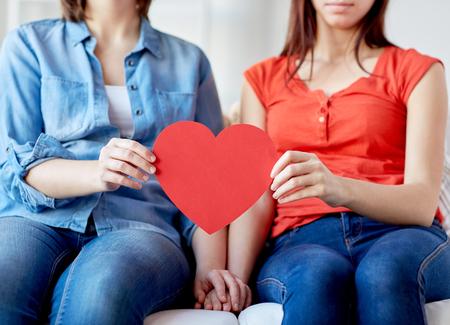 pareja casa: close up de la feliz pareja con corazones de papel rojo
