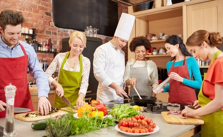 cooking chef: cooking class, culinary, food and people concept - happy group of friends and male chef cook cooking in kitchen Stock Photo