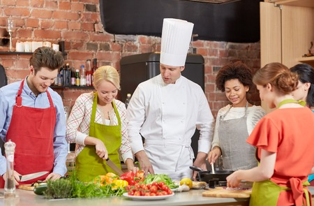 international food: cooking class, culinary, food and people concept - happy group of friends and male chef cook cooking in kitchen Stock Photo