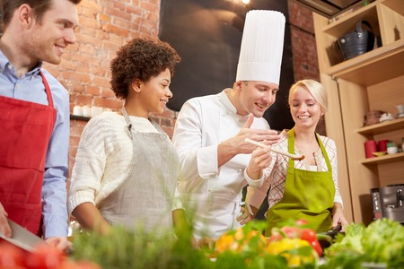 degustating: cooking class, culinary, food and people concept - happy group of friends and male chef cook cooking in kitchen Stock Photo