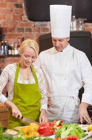 amateur: clase de cocina, culinario, comida y gente concepto - cocinero feliz Cocinero de sexo masculino con la mujer cocina en cocina Foto de archivo