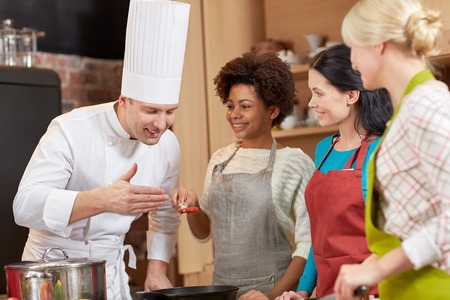 degustating: cooking class, culinary, food and people concept - happy group of women and male chef cook cooking in kitchen