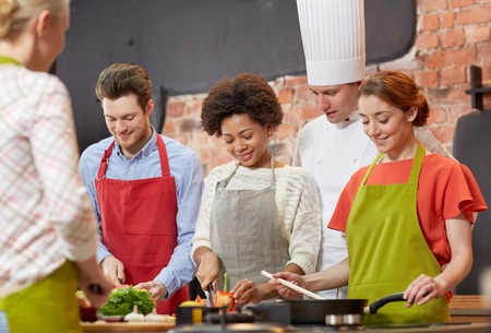 cooking class, culinary, food and people concept - happy group of friends and male chef cook cooking in kitchen Stock Photo