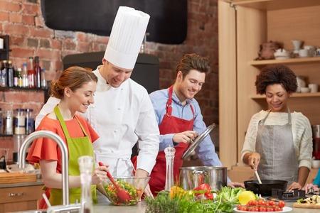 kulinarne: Klasa gotowanie, kulinarne, jedzenie i ludzie koncepcja - happy grupa przyjaciół i mężczyzn kucharz kucharz w kuchni Zdjęcie Seryjne