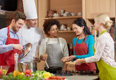 culinary: cooking class, culinary, food and people concept - happy group of friends and male chef cook cooking in kitchen Stock Photo