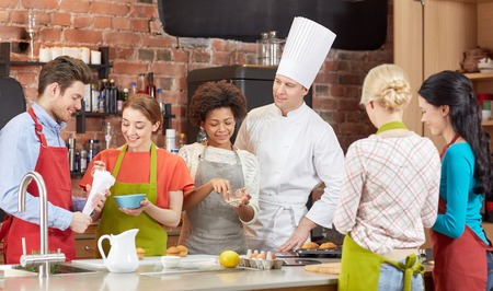 cooking class, culinary, bakery, food and people concept - happy group of friends and male chef cook baking in kitchen