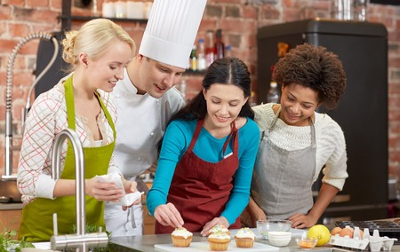 cooking class, culinary, bakery, food and people concept - happy group of women and male chef cook baking in kitchen Stock Photo
