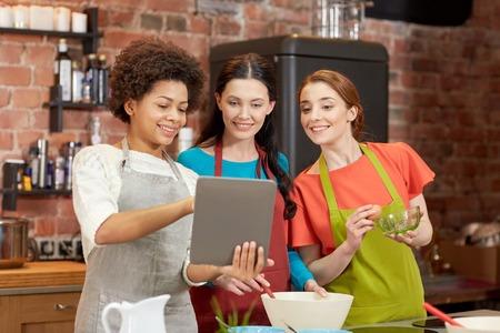 clases: clase de cocina, la amistad, la comida, la tecnolog�a y la gente concepto - mujer feliz con ordenador Tablet PC en la cocina