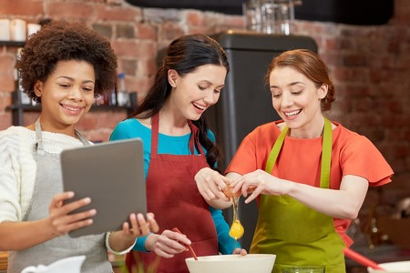 food technology: cooking class, friendship, food, technology and people concept - happy women with tablet pc in kitchen